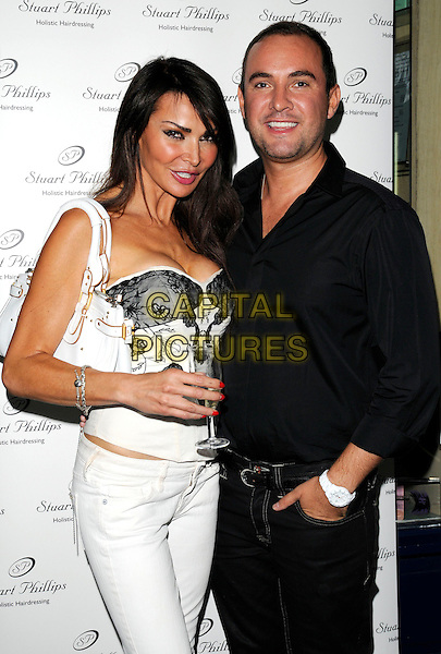 LIZZIE CUNDY & NICK EDE .Stuart Phillips Salon 15th Anniversary Party at Covent Garden, London, England, UK, July 15th 2009.half length liz white jeans black lace strapless top bustier corset cleavage glass bag drink.CAP/CAN.©Can Nguyen/Capital Pictures