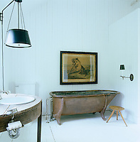 In the bathroom the antique oak-rimmed bath is made of galvanised iron with a large framed animal print hanging above