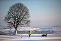 27/12/14<br /> <br /> A man walks his dog in Pomeroy in Derbyshire Peak District after heavy overnight snowfall.<br /> <br /> All Rights Reserved - F Stop Press. www.fstoppress.com. Tel: +44 (0)1335 300098