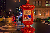 """An FDNY street fire alarm box in the Chelsea neighborhood of New York on a rainy Tuesday. January 14, 2014 evening. Because of an infrastructure failure, all 1,400 street fire alarm boxes in the borough of Manhattan are out of service requiring fire reporting via the 9-1-1 system.  Previous mayors have attempted to remove the boxes saying that they are obsolete and generate false alarms. Only two percent of all calls come from these boxes and of the two percent, 96 percent are false alarms. Verizon is attempting to get the boxes back in service. Hearing impaired are to use the """"9-1-1 tapping protocol"""". (© Richard B. Levine)"""