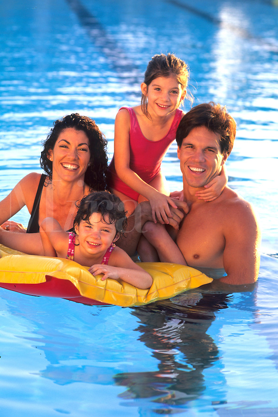 Hispanic Family in colorful pool on raft and hugging