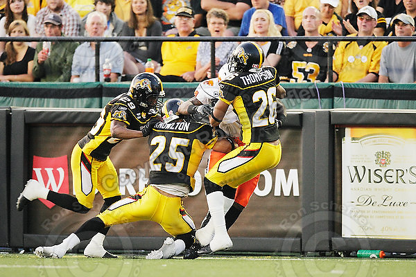 July 31, 2009; Hamilton, ON, CAN; Hamilton Tiger-Cats defensive back Lawrence Gordon (29), linebacker Markeith Knowlton (25) and defensive back Chris Thompson (26) tackle BC Lions wide receiver Emmanuel Arceneaux (84). CFL football: BC Lions vs. Hamilton Tiger-Cats at Ivor Wynne Stadium. The Tiger-Cats defeated the Lions 30-18. Mandatory Credit: Ron Scheffler. Copyright (c) 2009 Ron Scheffler.