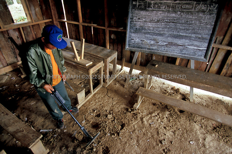 Phonsavan, Laos..A MAG worker searches a classroom for hidden bomblets under the ground. ..All photographs ©2003 Stuart Isett.All rights reserved.