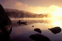 AJ1010, Vermont, canoe, canoeing, Woman paddles canoe in the early morning [fog, mist] on Kettle Pond at[sunrise, sunset] in Groton State Forest. Mad River Canoe Products.