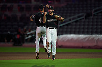 Fayetteville Woodpeckers first baseman Humberto Castellanos (45) and third baseman David Hensley (48) celebrate after closing out a Carolina League game against the Down East Wood Ducks on August 13, 2019 at SEGRA Stadium in Fayetteville, North Carolina.  Fayetteville defeated Down East 5-3.  (Mike Janes/Four Seam Images)