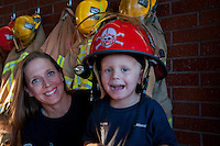 Phoenix fire captain Nicole Minnick, helps her son Taylor, 3, try on her back-up helmet in a Phoenix firehouse.  Minnick is one of many moms in the Valley who balance the 24-hour shifts of the fire department with raising children. Her back-up helmet sports a Nebraska Cornhuskers logo.