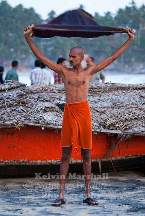 An Indian man starting to exercise on the beach.  Kovalam beach, Kerala - Southern India