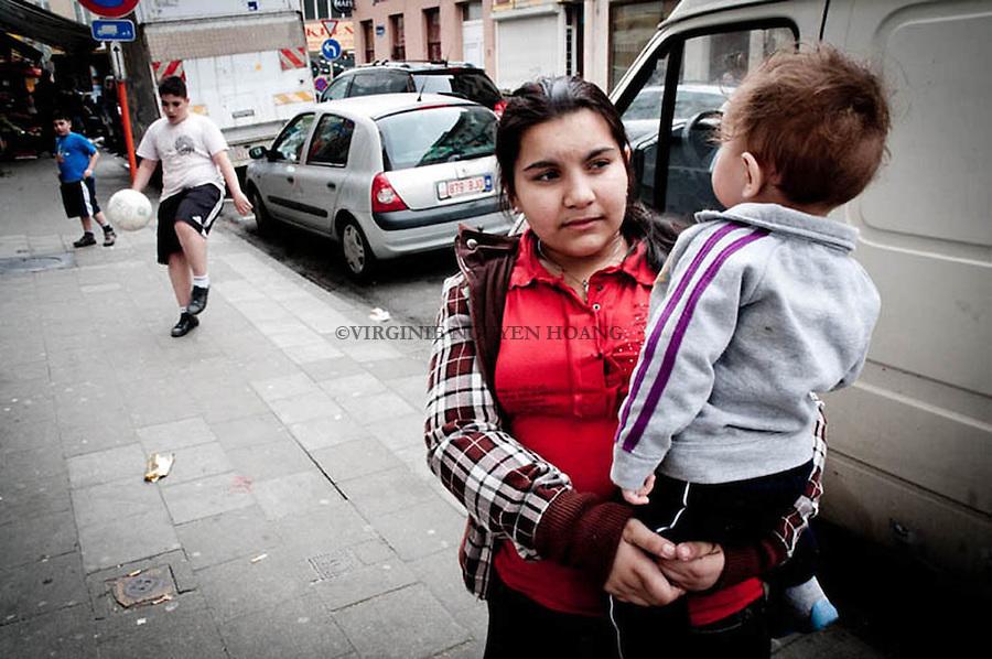 Instead of playing with other children, Sibianca takes care of her brother..A la place de s'amuser avec les autres enfants, Sibianca prends soin de son petit frère.