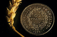 Ear of wheat next to a French fifty franc coin.