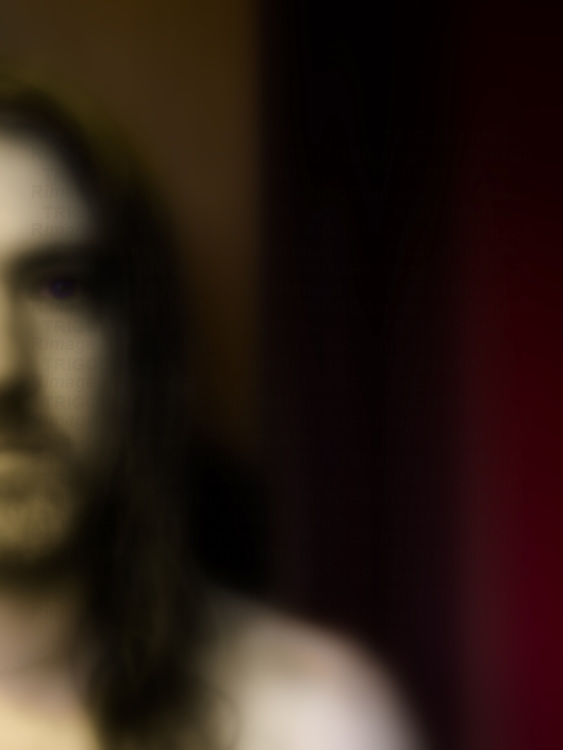 Half face portrait of long haired man in front of curtain.
