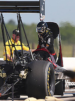 Apr. 28, 2013; Baytown, TX, USA: The blower and injector sits sideways on top of the motor of NHRA top fuel dragster driver Spencer Massey after an explosion as a member of the safety safari tends to him during the Spring Nationals at Royal Purple Raceway. Mandatory Credit: Mark J. Rebilas-