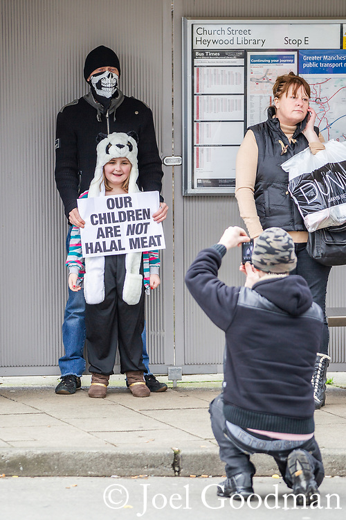 "© Joel Goodman - 07973 332324 . 03/03/2012 . Heywood , UK . A man holds a placard in front of a young girl that reads "" Our children are not halal meat "" as another man takes a photo of the two . The National Front hold a rally in protest against an alleged paedophile ring that had been operating in the area . There is currently (3rd March 2012) a case being tried at Liverpool Crown Court in relation to the allegations . Last Thursday (23rd February 2012) a protest organised in the town in relation to the same story resulted in Asian business being attacked by an angry mob . Photo credit : Joel Goodman"