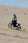 Dirt bike stands as he rides on the Oregon Dunes
