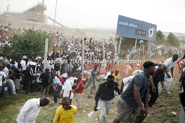 JOHANNESBURG, SOUTH AFRICA - DECEMBER 9: Thousands of soccer fans leave FNB stadium after a derby between local teams Kaizer Chiefs and Orlando Pirates on December 9, 2006 in Johannesburg, South Africa. Soccer is the most popular sport in South Africa, and a because of the upcoming World Cup 2010, the interest is increasing. For the first time the World Cup will be held on the African continent. This was the last game played on the stadium before construction started on the upgrading before the 2010 World Cup. This stadium will be the venue for the World Cup final game. (Photo by Per-Anders Pettersson).....