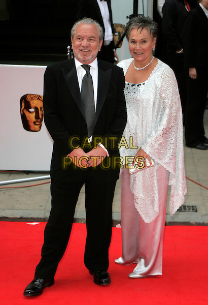 SIR ALAN SUGAR & WIFE.Red Carpet Arrivals at The British Academy Television Awards (BAFTA's) Sponsored by Pioneer, held at the London Palladium, London, England, May 20th 2007. .full length black suit white dress wrap shawl married couple.CAP/AH.©Adam Houghton/Capital Pictures.