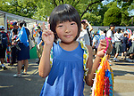 A girl displays folded paper cranes she has brought to Hiroshima in commemoration of the 70th anniversary of the U.S. dropping an atomic bomb on the Japanese city of Hiroshima. The cranes are a sign of hope and peace.