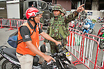 16 MAY 2010 - BANGKOK, THAILAND: Thai soldiers send a motorcycle taxi from Phloen Chit Road near the Red Shirt camp in Bangkok Sunday. Thai troops and anti government protesters clashed on Rama IV Road again Sunday afternoon in a series of running battles. Troops fired into the air and unidentified snipers shot at pedestrians on the sidewalks. At one point Sunday the government said it was going to impose a curfew only to rescind the announcement hours later. The situation in Bangkok continues to deteriorate as protests spread beyond the area of the Red Shirts stage at Ratchaprasong Intersection. Many protests now involve people who have not been active in the Red Shirt protests and live in the area of Rama IV. Red Shirt leaders have called for a cease fire, but the government indicated that it is going to go ahead with operations to isolate the Red Shirt camp and clear the streets.      PHOTO BY JACK KURTZ