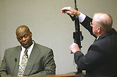 Robert Holmes of Tacoma, Washington, left, watches as Prince William County (Virginia) prosecutor Paul Ebert adjusts the bipods on the Bushmaster rifle used in the sniper shootings during the trial of sniper suspect John Allen Muhammad in Virginia Beach Circuit Court in Virginia Beach, Virginia on November 7, 2003. <br /> Credit: Tracy Woodward - Pool via CNP