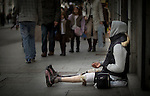 A woman with prosthetic legs begging on a street in central Madrid