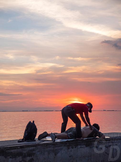 Massage along Manila Bay at sunset, Manila, Philippines all walks of life. Street Photography