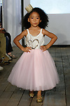 Child model walks runway in an outfit from the Belle Threads collection, during the KidFash Magazine runway show in Brooklyn, New York on Nov 4, 2017.