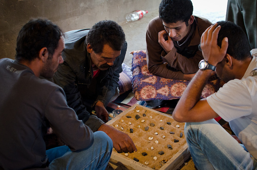 Men in Abu Tlul, an unrecognized Bedouin village in Israel's Negev Desert, play a board game with sand and stones.