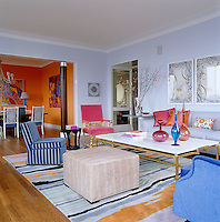 The open-plan living/dining area is large and spacious with the dining area painted a warm and vibrant orange in contrast to the cool blue tones of the living room