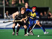 NZ's Ben Collier and Malaysia's Hafifi Hafiz Hanafi compete for the ball during the international hockey match between the New Zealand Black Sticks and Malaysia at Fitzherbert Park, Palmerston North, New Zealand on Sunday, 9 August 2009. Photo: Dave Lintott / lintottphoto.co.nz