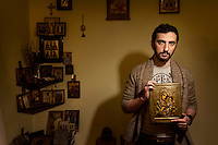 Dmitriy Tsorionov 'Enteo' stands holding an icon of Mary and the Christ Child in his Moscow home. Tsorionov is a radical Orthodox Christian who has staged several stunts to promote a creationist view point and to attack those he considers a threat to a Russia where church and state are closely linked such as LGBT people, Pussy Riot and secularists in general. (MANDATORY CREDIT   photo: Mads Nissen/Panos Pictures /Felix Features)