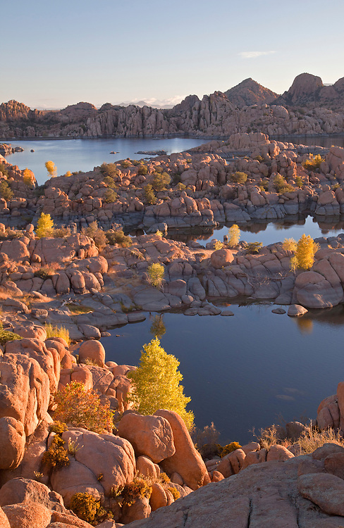 View of granite rocks and golden cottonwoods (Populus fremontii) during autumn at Watson Lake, Arizona, USA