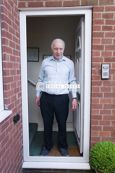 Older man standing outside his front door,