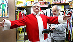 WATERBURY CT. 22 December 2017-122217SV07-Mike Patrick, Republican American, sees what it feels like to transform into Santa at Arabesque on Bank Street in Waterbury Friday. Michael Rinaldi, owner, left,  dressed Mike.<br /> Steven Valenti Republican-American