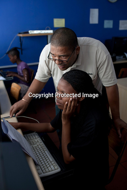 CAPE TOWN, SOUTH AFRICA - APRIL 20: Jonathan Loggenberg, a teatcher,shows an unidentified student work on a computer on April 20, 2012 in Cape Town, South Africa. They study for a certificate in basic computer knowledge. THe course is 3-6 months. The students come from poor backgrounds and have been unemployed until they come here. iThemba Labantu offers these young men and women the opportunity to learn a trade so that they will be able to earn a living for themselves and their families one day. (Photo by Per-Anders Pettersson For Global Post)