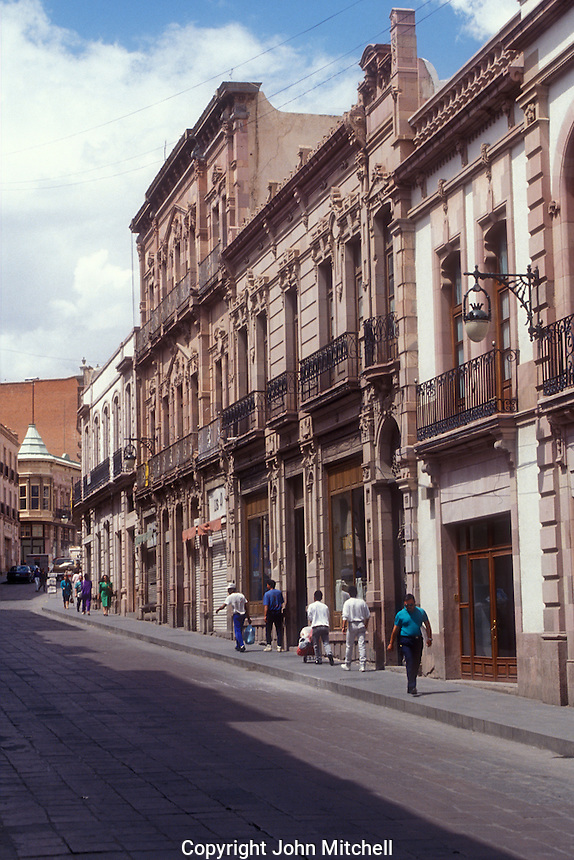 People walking down a street lined with Victorian era buildings in the city of Zacatecas, Mexico