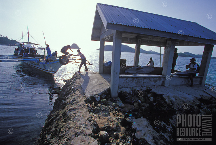 Surfers and passengers sitting in waterfront shelter waiting for interisland ferry, Philippines