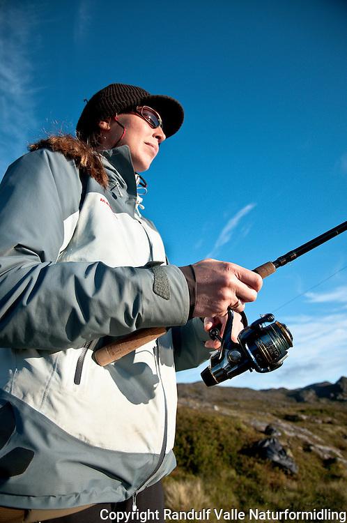 Dame fisker med haspelstang. ---- Woman spin fishing.