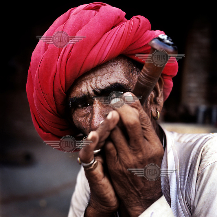 A Raika man smokes a tobacco chillum (pipe). The Raika are an ancestral caste of camel breeders in Rajasthan. Due to the increased cost of feeding and shelter, more and more Raika are being forced to sell off their camels, often for camel meat, which was once considered taboo.