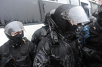 Berkut special police forces have frozen water on their uniforms after they have being sprayed with fire hydrants by the protesters in the  town hall. Kiev Ukraine.   The temperature on the street is 12 degrees C. below zero<br /> <br /> Protesters did not give up after the faint  attempt of evacuation performed by the police of the night before. Despite the adverse weather conditions,  they restored and rebuilt the complex structures of the  barricades under the snow in Maidan square. Kiev,  Ukraine.