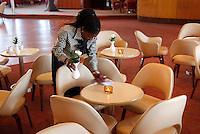 Serveerster maakt tafel schoon in het schip  de SS Rotterdam