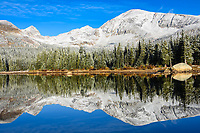 Dusted in their first snowfall of the year, the Indian Peaks rise above and reflect in Brainard Lake, Colorado.