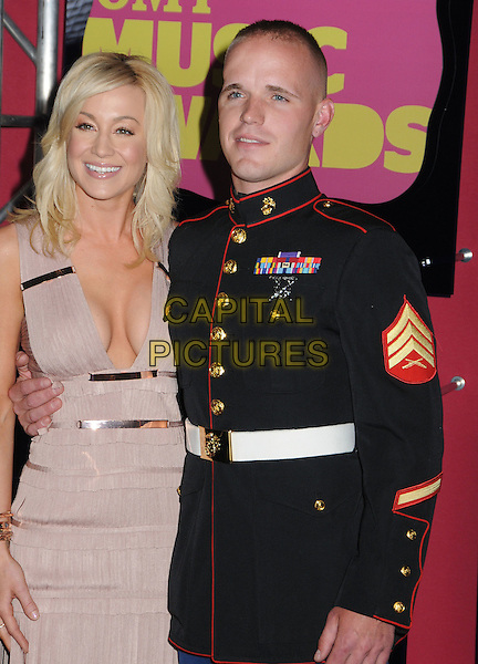 Kellie Pickler & guest.2012 CMT Music Awards held at Bridgestone Arena, Nashville, Tennessee, USA..June 6th, 2012.half length beige pink dress low cut neckline cleavage black uniform  .CAP/ADM/LF.©Laura Farr/AdMedia/Capital Pictures.