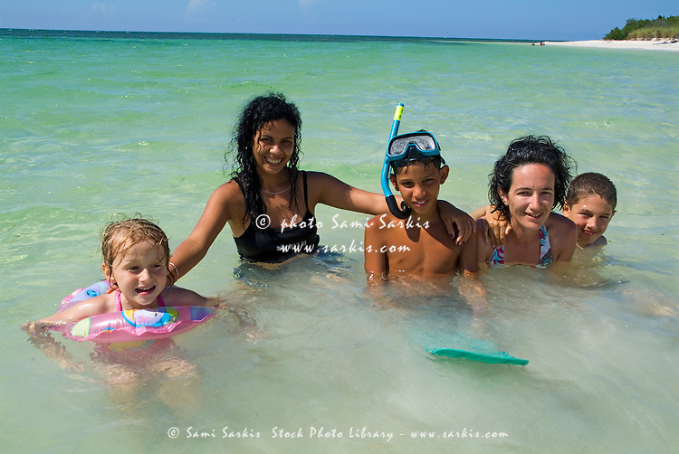 Cuban and European family bathing together, Cayo Jutias, Cuba.