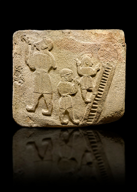 Upright picture of Alaca Hoyuk Sphinx Gate Hittite monumental relief sculpted orthostat stone panel. Andesite, Alaca, Corum, 1399 - 1301 B.C. Jugglers and acrobats.  Anatolian Civilizations Museum, Ankara, Turkey<br /> <br /> The juggler facing towards left, with long hair and a short dress, swallows a dagger; the smaller acrobats behind go up the stairs without holding on. All the figures have horned headdresses and earrings with a huge ring on their ears. It is thought that the acrobats are of different nationality, which is the reason why they are depicted smaller. <br /> <br /> Against a black background.