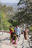 Nepal, Kathmandu, Swayambhunath.  Visitors Climbing the Steep Stairway to the Stupa.  Kathmandu in the distance.