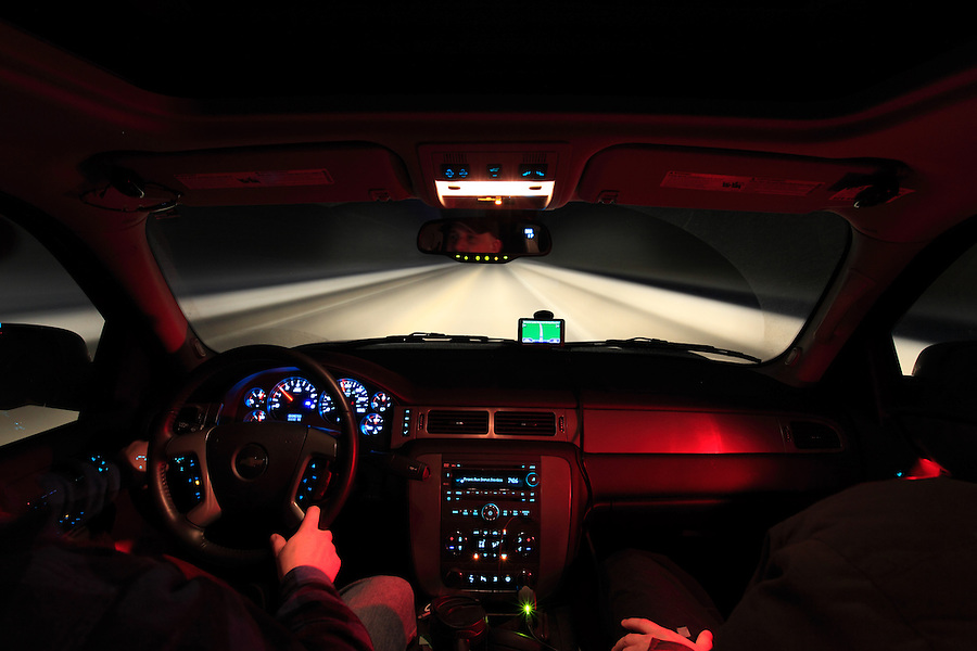 A driver and passenger are seen from the perspective of a rear observer on the interior of a Chevy Suburban driving a winter road in the evening.