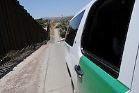 Nogales, Arizona - A Border Patrol vehicle rides along the international U.S.-Mexico border. The vehicle was part of a caravan that took journalists to the border in an event sponsored by the U.S. Customs and Border Protection agency. This area is near the Border Patrol Nogales station, one of eight in the Tucson Sector, which is the busiest on the U.S.-Mexico border for illegal immigration, drug smuggling and border deaths. Photo by Eduardo © 2012