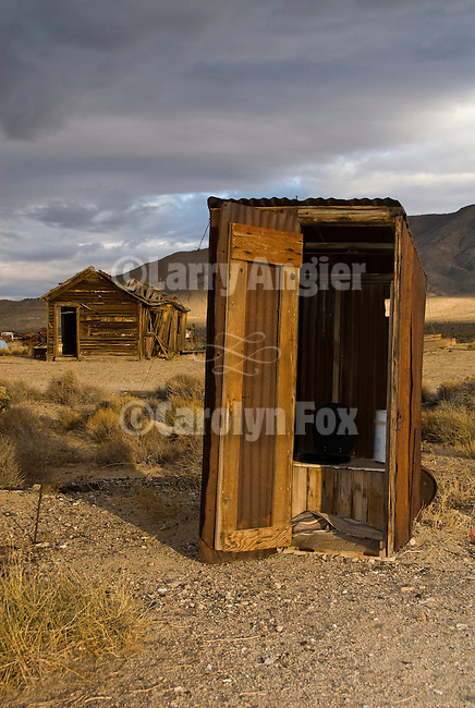 Corrugated open door outhouse and out buildings at a ghost town in Nevada