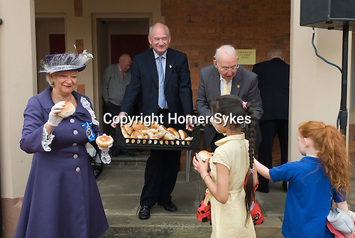 Bedworth Bun Day.  The Nicholas Chamberlaine's Legacy. High Sheriff Janet Bell Smith giving out buns.<br /> <br /> Nicholas Chamberlaine was the local landowner and rector at Bedworth Warwickshire  for over fifty year. On 24th June, 1715, Chamberlaine signed his will making  provision for the people of Bedworth.  He provided funds for the building of two schools and for Almshouses, he died three weeks later, on the 14th July, aged eighty-three. Founders Day is still celebrated annually, though it has evolved over the years and is now often referred to as Bun Day because the local schoolchildren are each given a current bun at the special service of hymns and prayers. Four Church of England schools take part, roughly 800 children. The buns are distributed on the lawn in front of the Almshouses by local   dignitaries