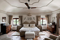 A perfectly symmetrical bedroom with the double bed placed between the windows and matching furniture on each side