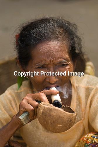 Older woman smoking a huge roll your own cigar at Nyaung-U market Bagan, Myanmar (Burma.) 2006